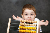Boy in surprise spread his arms near the wooden abacus. — Stock Photo