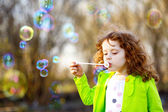 A little girl blowing soap bubbles, spring portrait beautiful cu — Stock Photo