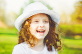 Portrait of curly smiling baby in white hat. — 图库照片