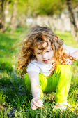 Little curly girl pluck yellow flowers. — Stock Photo