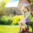 Little girl sits on a chair in the yard of a country house. — Stock Photo #49144605