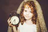 Curly girl holding alarm clock. Photo toned brown. — Stock Photo