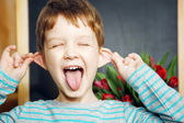 Happy Little boy, pulling himself on the ears and stuck out his — Stock Photo