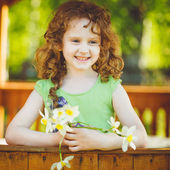 Curly baby with bouquet flowers in her hand. Toning photo. — Stock Photo
