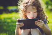 Little girl sitting on grass and playing tablet pc, toning photo — Stock Photo