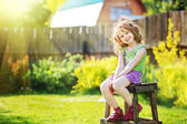 Little girl sits on a chair in the yard of a country house. — Stock Photo