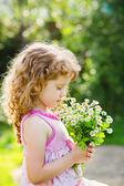 šťastné dítě v poli s kyticí daisy. tónování fotografií. — Stock fotografie