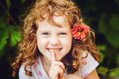 Beautiful little girl putting finger up to lips and ask silence. — Stock Photo