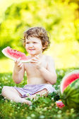 Happy little boy eating watermelon  in summer park.  — Stock Photo
