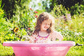 Happy curly girl taking water procedures in summer garden. — Stock Photo