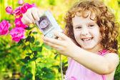 Šťastná holčička s vlastní fotografií na letní zahrada. — Stock fotografie