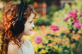 Little girl listening to music on headphones in a summer park. I — Stock Photo