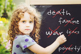 Girl writes in chalk on a blackboard. Peace concept. Toning phot — Stockfoto