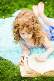 Little girl reading a book in the summer park, toning photo. — Foto de Stock