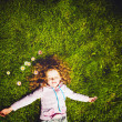 Curly girl lies on the grass and smiling, toning photo. — Stock Photo #51704811