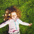 Curly girl lies on the grass and smiling, toning photo. — Stock Photo #51704819