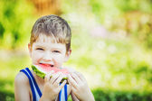 Child eating watermelon in summer park. — Stock Photo