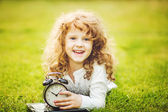 Girl lying on the grass and holding alarm clock. — Stock Photo