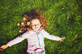 Curly girl lies on the grass and smiling, toning photo. — Stock Photo