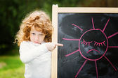 Little girl dissatisfied points on the board with a picture. Sad — Stock Photo