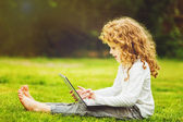 Happy surprised child with laptop sitting on the grass. — Stok fotoğraf