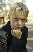 A boy in a suit looks thoughtfully. — Stock Photo