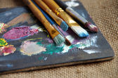 Brush in the paint on the palette — Stock Photo