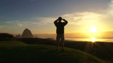 Man at Pacific Ocean near Cannon Beach looks out to sea as sun sets on beautiful day. — Stock Video