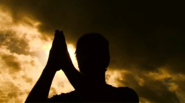 Person silhouetted separates praying hands to reveal sun shining through. — Stock Video