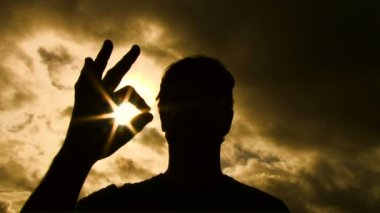 Person silhouetted raises hand into frame to give an a-okay sign with sun shining through to camera lens. — Stock Video
