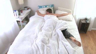 Hombre despierta y llega a dormitar en alarma y luego vuelve a dormir. — Vídeo de Stock