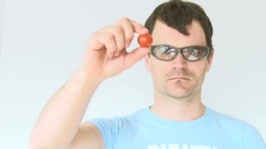 Funny tough guy squeezes small tomato which squirts him in the eye. — Stock Video