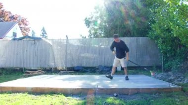 Model released man sweeping off dust from new concrete foundation, time lapse. — Stock Video