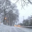 Blizzard conditions with vehicles driving on snow filled roads in Portland, Oregon. - Stock Photo