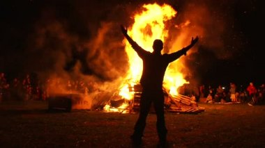 Man walks up to large fire and puts both arms up high. — 图库视频影像