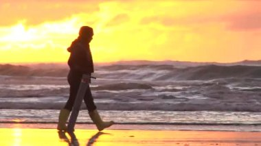 Woman with clamming gun walk Pacific Ocean in search for razor clams at sunset, zoom out and tilt up to sky. — Stock Video