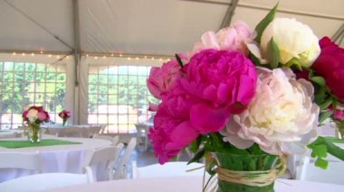 Tented wedding setting viewing large floral centerpieces . — Stock Video