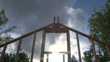Time Lapse of clouds and sun shining through window on framework of new construction. — Stock Video