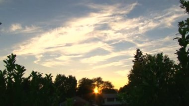 Sun goes down through trees at sunset with beautiful clouds time lapse. — Stock Video