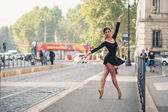 Young ballerina dancing along the street — Stock Photo