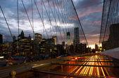 Horizonte de manhattan desde el puente de brooklyn al atardecer con coches tra — Foto de Stock