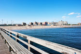 Pier with Coney Island beach in the background, New York City. — Stock Photo