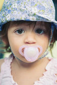 One year old girl with pacifier outdoor portrait. — Stock Photo