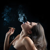 Woman smoking cigar against dark background. Studio fashion phot — Stock Photo