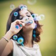 Romantic portrait of young woman with soap balloons. — Stock Photo #14440461