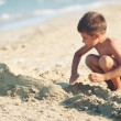 Kid playing on the beach in a sunny day. — Stock Photo