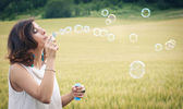Romantic portrait of young woman with soap balloons. — Stock Photo