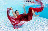 Underwater woman fashion portrait with red veil in swimming pool — Stock Photo