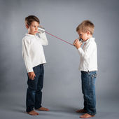 Young brothers talking with tin can telephone. — Stock Photo