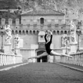 Young beautiful ballerina jumping along Castel Santangelo bridge — Stock Photo